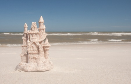A sandcastle on the beach with blue sky behind it