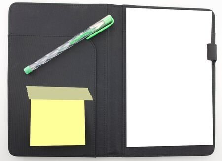 Business agenda planner with paper and a green pen. Post it notes