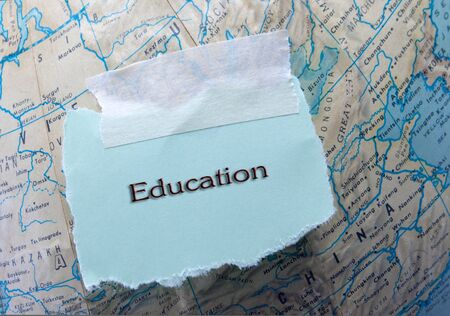 Education written on a blue piece of torn paper on top of a globe
