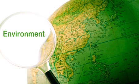 A green globe with a magnifying glass looking at the word environment