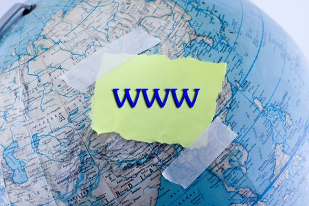 WWW written on a yellow torn piece of paper over top a globe