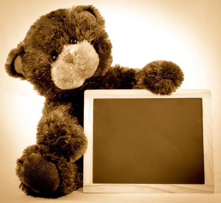 A brown bear holding a blank chalkboard Stock Photo