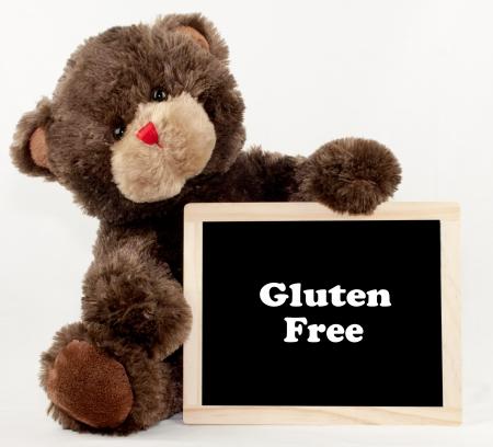 A brown bear holding a gluten free chalkboard
