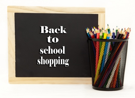 Back to school shopping chalkboard with colored pencils in a holder