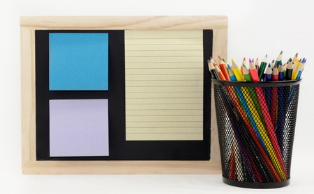 A chalkboard with blank paper and colored pencils in a holder Stock Photo - 16259366