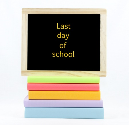 Last day of school text on a chalkboard on top of colored books