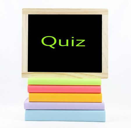 Quiz text on a chalkboard on top of colored books