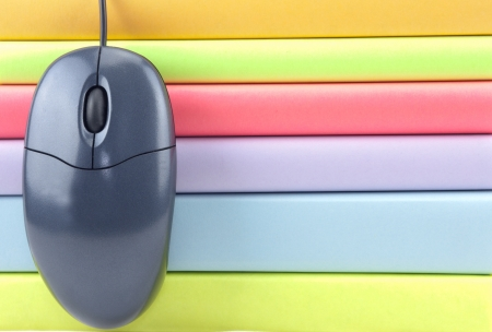 A close up of a computer mouse hanging over colored books Stock Photo