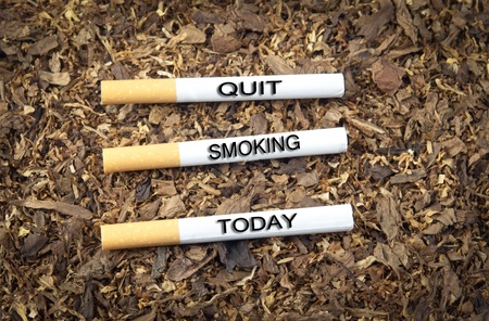 Three cigarettes with text quit smoking today on top of tobacco Banco de Imagens