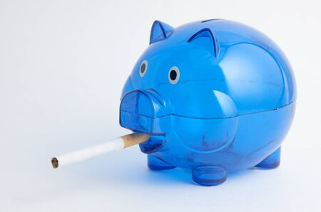 A blue piggy bank smoking a cigarette Stock Photo