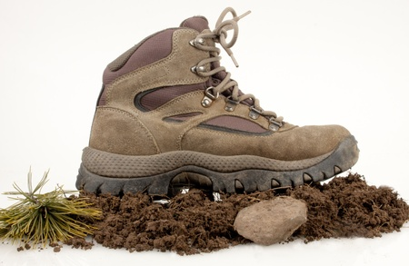 Hiking boot on dirt ,stone and green leaves isolated on white