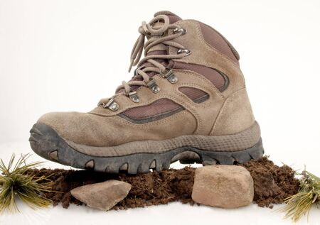 Hiking boot on top of dirt, rocks and green leaves isolated on white Stock Photo