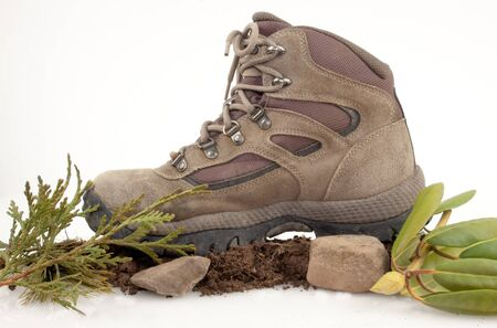Hiking boot on dirt ,stones and green leaves isolated on white Stock Photo - 17089786