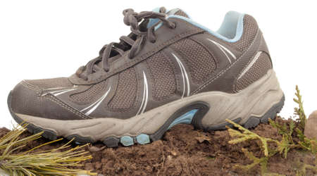Sneaker on top of dirt ,rock and green leaves isolated on white Stock Photo - 17089776