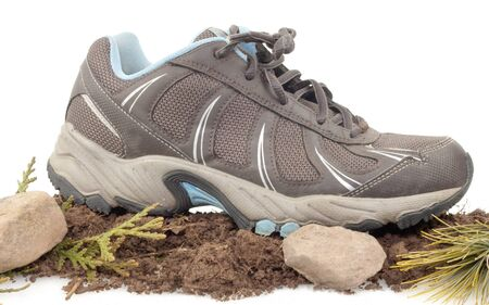 Sneaker on top of dirt ,rocks and green leaves isolated on white Stock Photo - 17089779