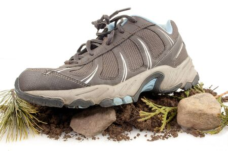 Side view of sneaker on top of rocks, dirt and green leaves isolated on white