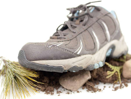 Front view of sneaker on rocks,dirt and green leaves isolated on white Stock Photo - 17089765