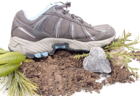 Sneaker on top of dirt with a heart shaped rock and green leaves isolated on white Stock Photo - 17089783