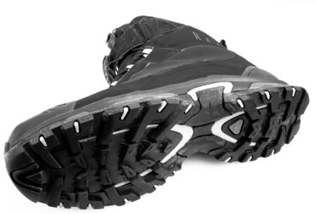 tred: Bottom view of a black hiking boot isolated on white