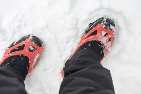 Hiker wearing a pair of crampons in the snow