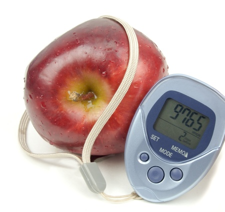 String from a blue pedometer wrapped around an apple isolated on white