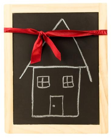 Una casa disegnata su una lavagna avvolto con un nastro rosso photo