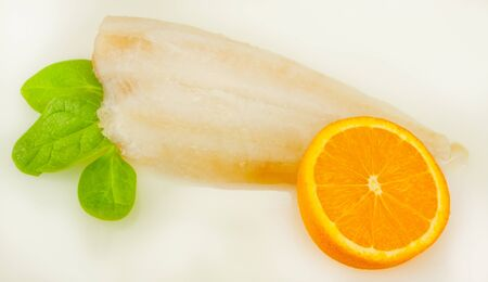 A piece of fish with spinach leaves and a slice of orange Stock Photo - 18968700