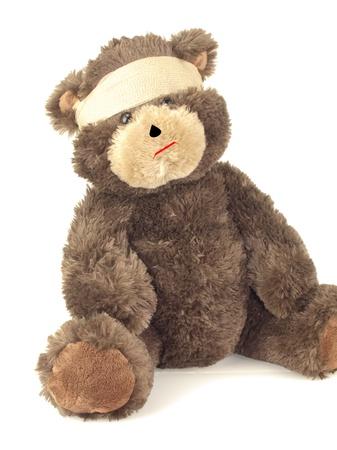 Een gewonde opgezette beer verpakt in een ace verband rond zijn hoofd op wit wordt geïsoleerd