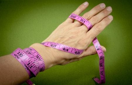 背景が緑色の手を包んだ測定テープ 写真素材