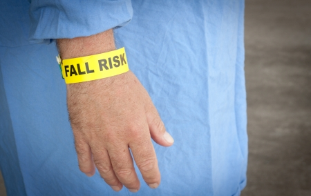 physical therapy: A patient wearing a fall risk bracelet in a blue gown