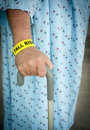 An elderly man wearing a fall risk bracelet around his wrist at the hospital. Wearing a blue gown and walking with a cane.