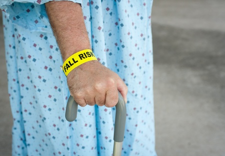 hospital gown: An elderly man wearing a fall risk bracelet around his wrist at the hospital. Wearing a blue gown and walking with a cane.