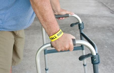 An elderly man wearing a fall risk bracelet around his wrist using a walker Stock Photo