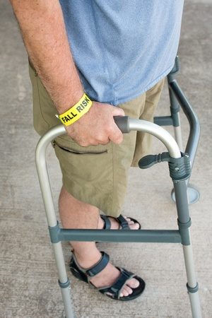 A man wearing a fall risk bracelet around his wrist using a walker Stock Photo