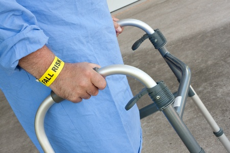 A hospital patient wearing a fall risk bracelet using a walker Stock Photo
