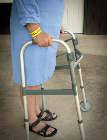 A person wearing a fall risk bracelet while walking with a walker