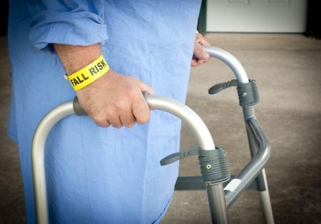 Een patiënt lopen met een rollator met een valrisico armband en blauwe jurk