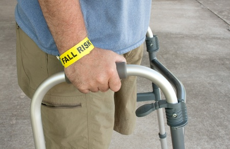 A handicap man wearing a fall risk bracelet around his wrist using a walker