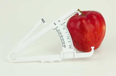 A weight caliper tool measuring a red apple isolated on white photo