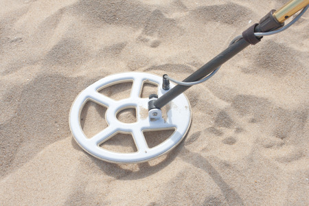A metal detector in the sand looking for jewelry and coins Stock Photo