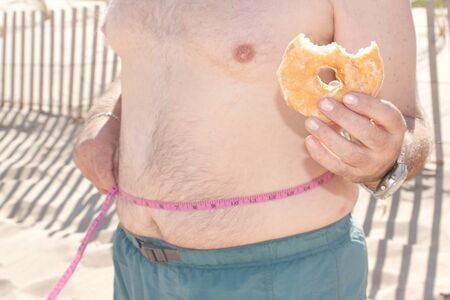 A man eating a donut with a weight tape measure around his waist at the beach
