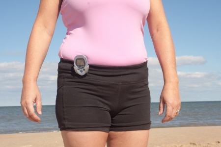 Woman wearing a pedometer walking on the beach