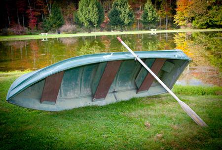 changing color: Un bote con un remo en un lago en la temporada de oto�o con los �rboles y las hojas cambian de color Foto de archivo