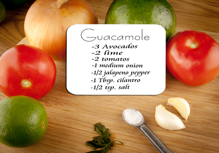 Guacamole ingredients on a cutting board with a recipe card