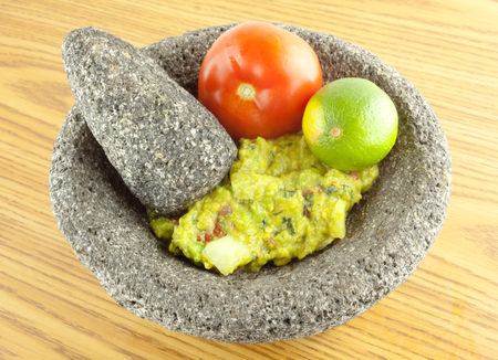 Molcajete mortar bowl and pestle filled with guacamole, tomato,and lime on a wooden table