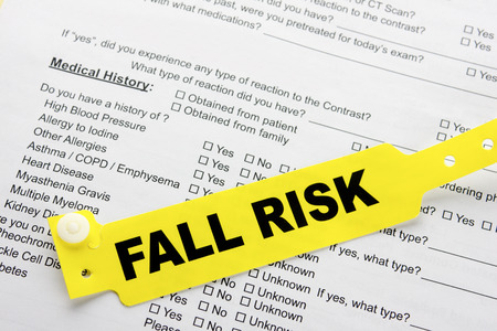 A yellow fall risk patient bracelet on top of a hospital questionnaire paperwork photo