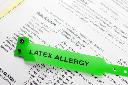 A latex allergy patient bracelet on top of a hospital questionnaire paperwork Stock Photo