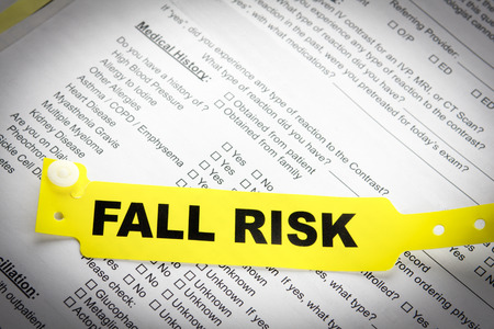 A yellow fall risk patient bracelet on top of a hospital questionnaire paperwork Stock Photo - 27281463