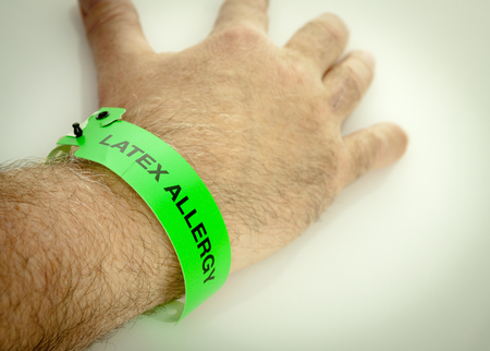 A hand with a green latex allergy bracelet around wrist Stock Photo