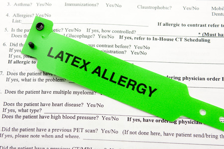 A green latex allergy patient bracelet on top of a hospital questionnaire paperwork